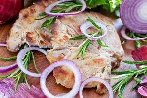 plakjes gegrild varkensvlees met ui en rozemarijn op hout foto