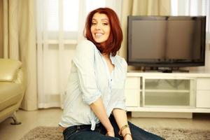 lachende vrouw zittend op het tapijt
