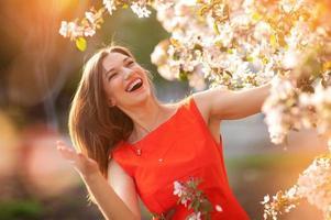 mooie jonge donkerbruine vrouw die zich dichtbij de bloeiende boom bevindt foto