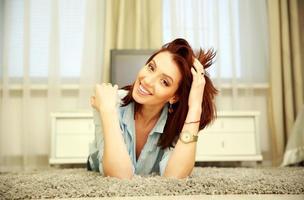 gelukkige vrouw die op de vloer rust