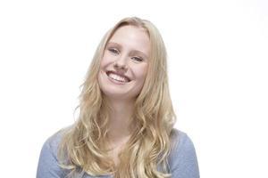 jonge blonde vrouw die lacht tegen een witte achtergrond foto