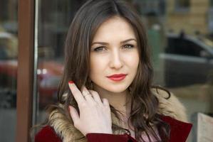 mooie jonge vrouw in rode jas en haar glimlach foto