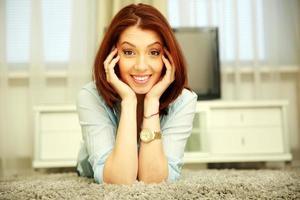 glimlachende vrouw die op de vloer rust
