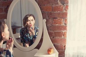 mooie vrouw make-up haar lippen en op zoek naar de spiegel foto