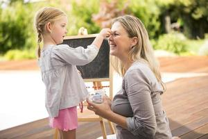 jong meisje en moeder buiten spelen, schoolbord op achtergrond foto