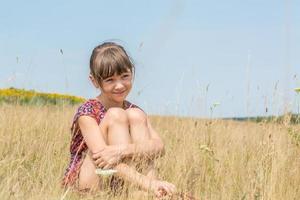 mooi schattig meisje zitten onder in het veld foto