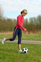 Sportvrouw een bal schoppen foto