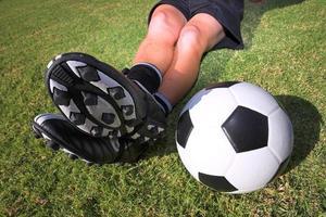 voetballer met een voetbal op voetbalveld foto