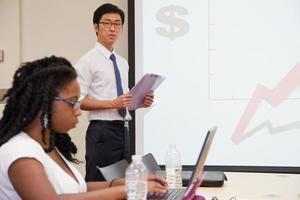 presentator presenteert & studenten werken in internationale klaslokaal
