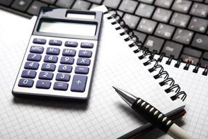 pen met rekenmachine op een notebook en toetsenbord foto