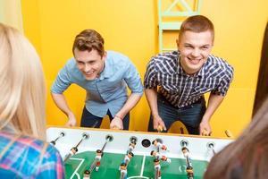 gelukkige vrienden spelen tafel hockey foto