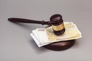 rechter hamer en eurobankbiljetten geïsoleerd op grijs foto