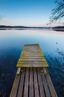 meer landschap met kleine houten pier gefotografeerd op lange blootstelling