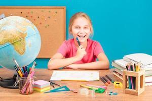 jong glimlachend meisje dat haar huiswerk doet foto