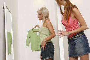 jonge vrouwen kijken naar winkel spiegels