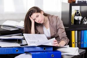 zakenvrouw met zoveel papierwerk op kantoor foto