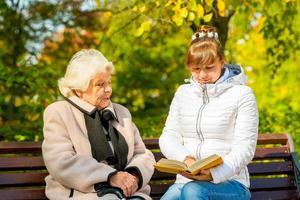 jonge kleindochter leest zijn bejaarde oma-boek