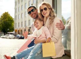 gelukkig gezin met kind en boodschappentassen in de stad foto