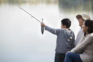 jongen visserij vangst met familie bij meer bewonderen foto