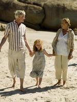 meisje lopen op het strand met haar grootouders.