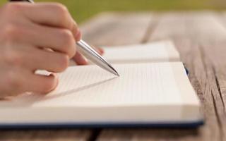 close-up van de mens het schrijven van notities op houten tafel. foto