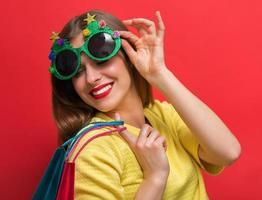 vrouw met kerstfeest bril en boodschappentassen foto