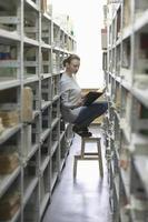 vrouw leesboek in bibliotheek gangpad foto
