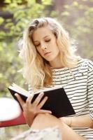 jonge vrouwelijke student studeert in het park foto