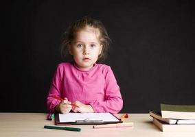 klein meisje tekenen in de klas foto
