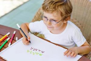 kleine jongen met een bril huiswerk thuis foto