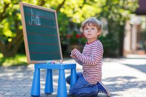kleine jongen op schoolbord het beoefenen van wiskunde