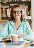 gelukkig studentenmeisje met boek en koffie in bibliotheek foto