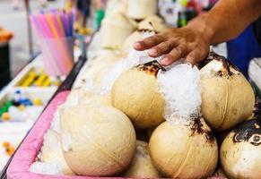 jonge kokosnoot drankjes op straat foto