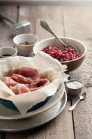rauw varkensvlees in een kom, veenbessen en vleeshamer foto