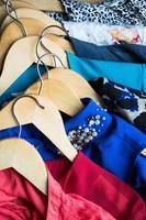 verschillende kleding op hangers close-up foto
