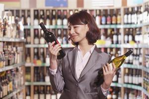 medio volwassen vrouw die wijn in een slijterij kiest foto