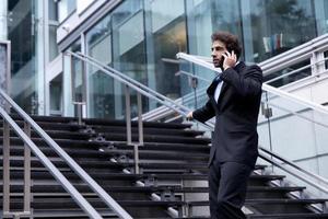 trotse zakenman aan de telefoon voor zijn kantoor foto
