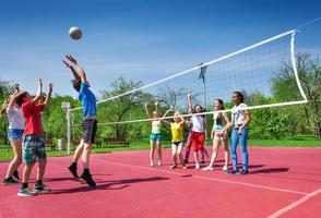 springende jongen tijdens volleybalwedstrijd op het veld foto