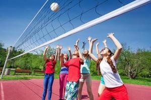 groep tieners met armen omhoog volleyballen foto