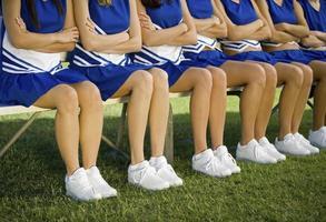 cheerleaders zitten met gekruiste armen op bankje in veld foto