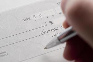 zakenvrouw voorbereiden het schrijven van een cheque foto