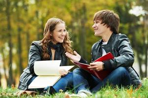 twee lachende jonge studenten buitenshuis foto