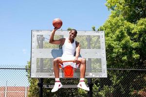 kampioen basketbalspeler zitten in de hoepel foto