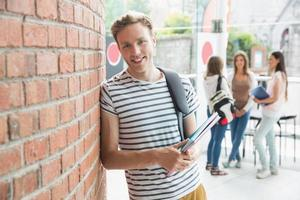 knappe student die en blocnotes glimlacht houdt foto