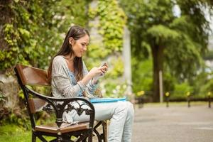 lachende student zittend op bankje op de universiteit foto