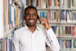 knappe student met behulp van mobiele telefoon in bibliotheek foto