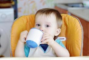 baby drinken uit beker foto