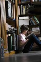 jong meisje leesboek in bibliotheek foto
