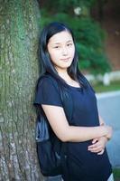 Aziatisch schoolmeisje buitenshuis foto