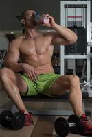 bodybuilder die wei-eiwit drinkt foto